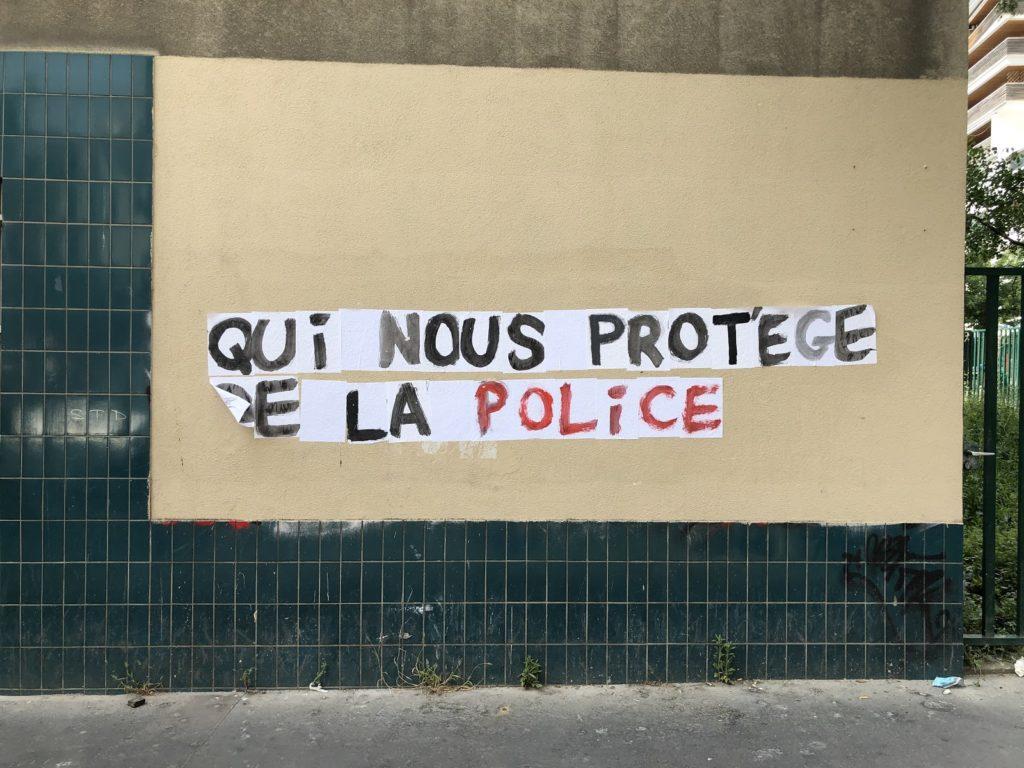 """Collage du slogan """"Qui nous protège de la police""""."""
